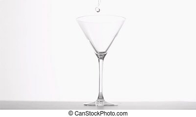 Gin poured in super slow motion against white background