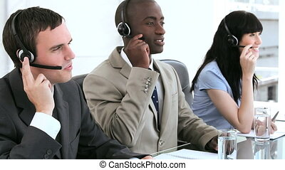 Happy call centre agents working together with headsets