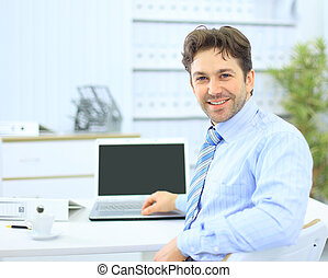 Business man sitting at his desk in the office with a laptop
