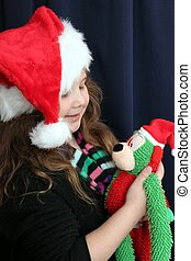 Pretty little girl with Santa hat and stuffed animal