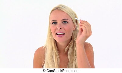 Blonde woman using tweezers against white background