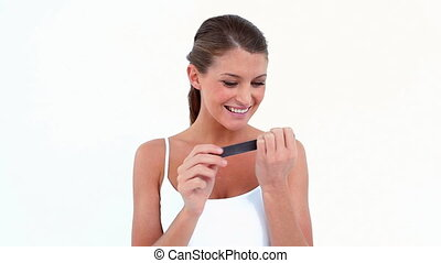 Woman using a nail file against white background