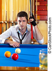 Billiard expertise man posing on blue with alcohol on the...