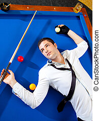 billiard young man player lying on pool blue table with...