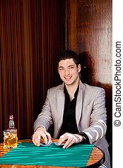 Latin handsome gambler man in table playing poker