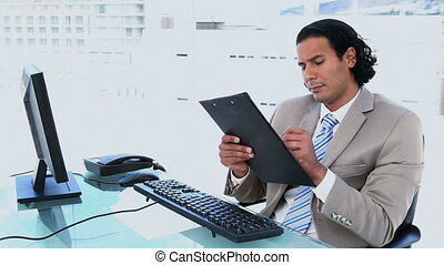 Businessman giving a clipboard to someone in a bright office
