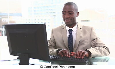 Black businessman typing on a keyboard in his office