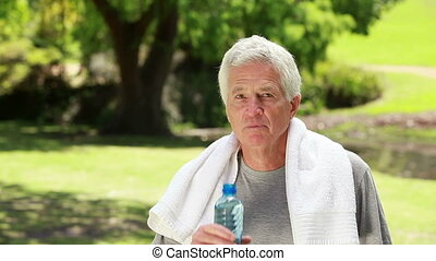 Smiling mature man drinking water