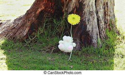 Smiling girl holding a flower and a teddy bear in a parkland