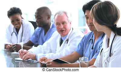 Mature doctor talking with his colleagues in a bright office