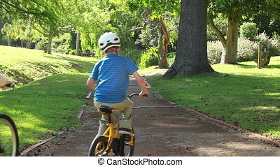 Boy riding a bike with his parents on a pathway in a park