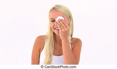 Woman using a cotton pad on her eye against white background