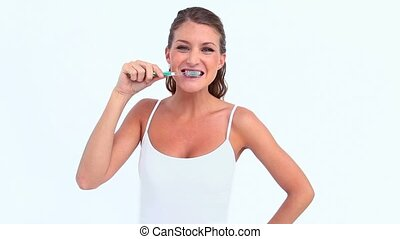 Woman brushing her teeth against white background
