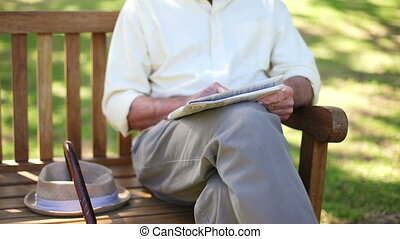Retired man with a newspaper sitting on a bench