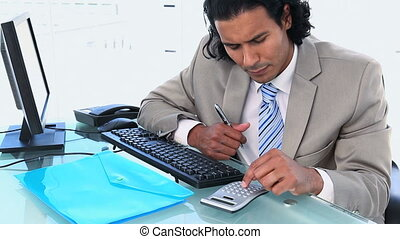 Latin businessman using a calculator while sitting at his...