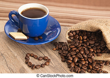 Cup of coffee with beans on old wooden surface