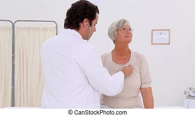 Practitioner examining his mature patient