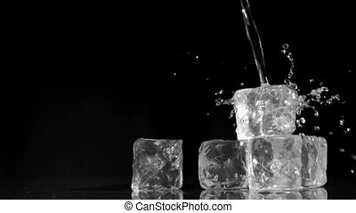 Water being poured in super slow motion onto ice cubes...