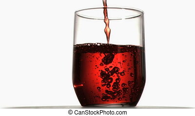 Red liquid in super slow motion flowing in a glass against a...