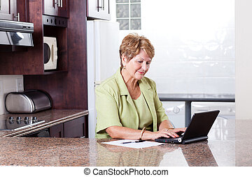 senior woman using internet banking at home