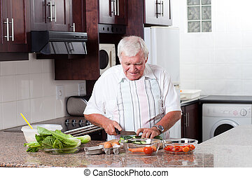 elderly man cooking in home kitchen
