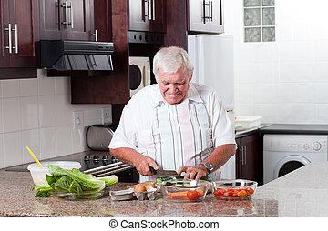elderly man cooking in home kitchen
