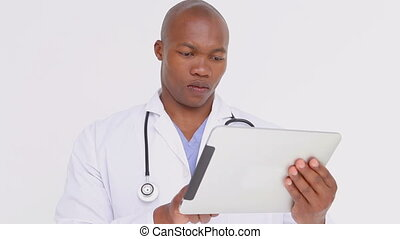 Serious doctor standing while holding a tablet pc against a...