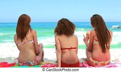 Three women sitting on towels on the sand turn around...