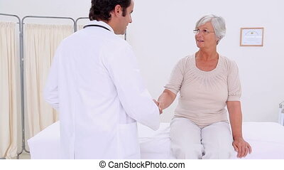 Mature woman sitting while being examined in a medical...