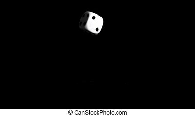 One dice in super slow motion bouncing against a black...
