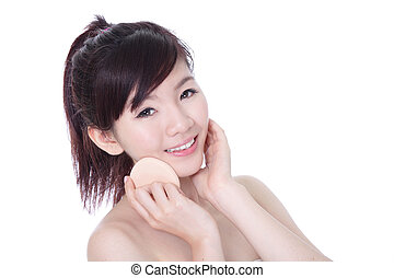 Woman using cosmetic sponge on face with smile - Beautiful...