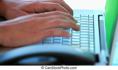 Close-up on hands typing on a keyboard and picking up the...