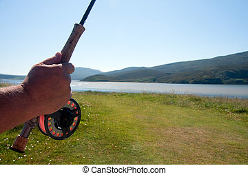 Fishing rod - hand holding a fly fishing rod