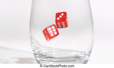 Two red dices in a super slow motion turning in tumbler glass
