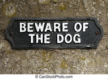 Beware of the dog sign screwed onto stone