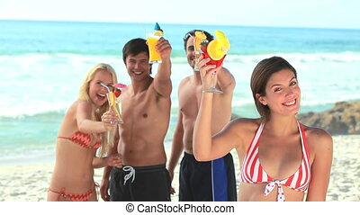 Friends all enjoying cocktails in swimwear at the beach