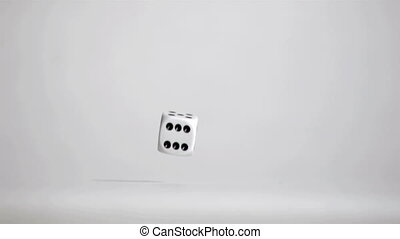 One white dice in super slow motion rebonding on the grey floor