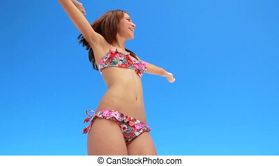Woman dancing in her bikini at the beach
