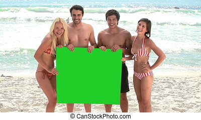 Smiling friends holding a blank poster together on the beach