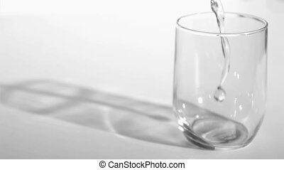 Trickle of water in a super slow motion flowing into a glass