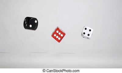 Three black red white dices in a super slow motion rebonding