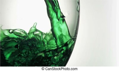 Green trickle in a super slow motion flowing in a glass