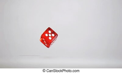 One red dice in a super slow motion rebounding and turning