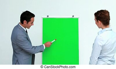 Businessman explaining something on a board to a colleague