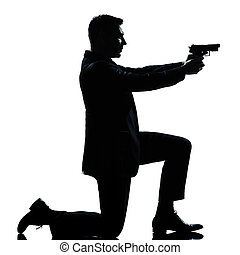 silhouette man kneeling aiming gun - one caucasian spy...