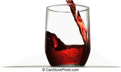 Red soda in super slow motion flowing in a glass against a...