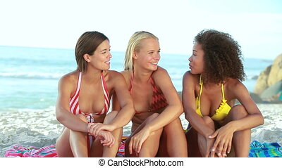 Women sitting at the beach together