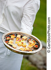 catering appetizer - a waiter serving appetizers at a...