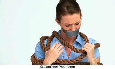 Businesswoman attached with a rope and having tape on her...