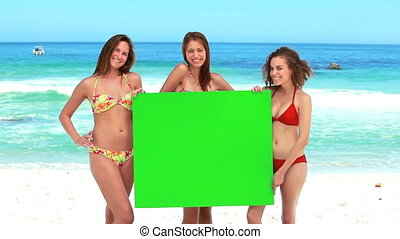 Three girls hold a green screen